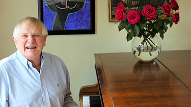 Composer Paul Williams seated at his grand piano on which is a vase of red roses